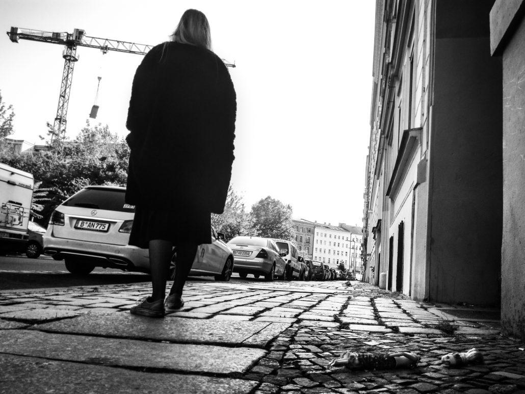 Woman walking next to a broken doll